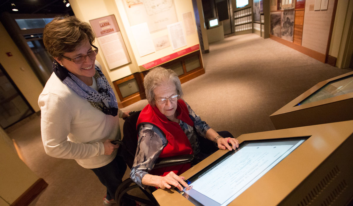 Museum visitor in a wheelchair and guest interact with an exhibit in the Public Vaults.