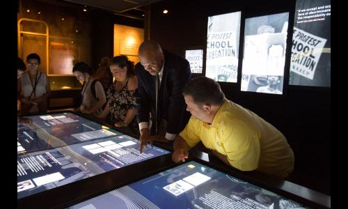 Museum visitors explore the interactive touch screen table in the Records of Rights Exhibit
